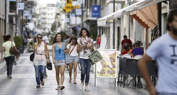 Pedestrians pass restaurants and shops as they walk along a shopping street in Pescara, Italy