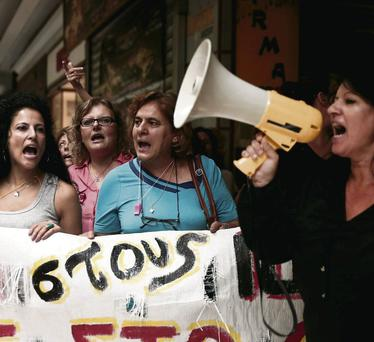 Cleaners employed at the Greek finance ministry shout slogans during a rally against job cuts in their sector outside the ministry in Athens this week