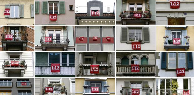 A composite image of flags on houses in Berne and Zurich supporting the proposal to limit the pay of top executives