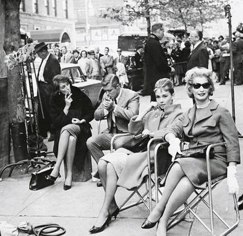 Actors take a break on a New York Street, during location filming for 'Breakfast At Tiffany's' near the iconic New York store. Centre left is leading man, George Peppard and centre right is Audrey Hepburn who played Holly Golightly