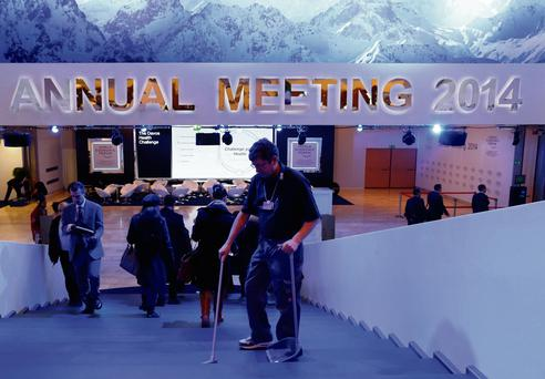 SLIPPERY SLOPE: A staff member cleans a stair inside the congress centre at the annual meeting of the World Economic Forum in Davos. Photo: Ruben Sprich/Reuters