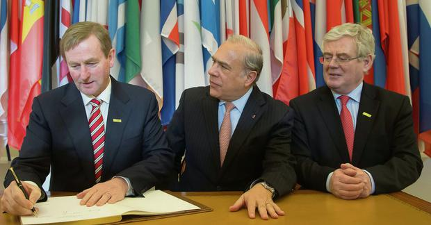 Enda Kenny, left, signs the golden book while the head of the Organization for Economic Co-operation and Development (OECD) Angel Gurria, center, and Ireland's Minister for Foreign Affairs and Trade, Eamon Gilmore, right, sit next to him at the OECD headquarters in Paris