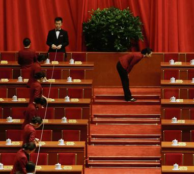 Attendants adjust tea cups before the opening ceremony of Chinese People's Political Consultative Conference (CPPCC) at the Great Hall of the People in Beijing.