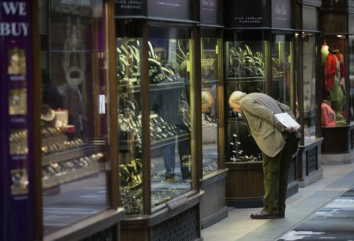 A pedestrian looks at rings and watches displayed in the window of a jewellery store in the Burlington Arcade in London