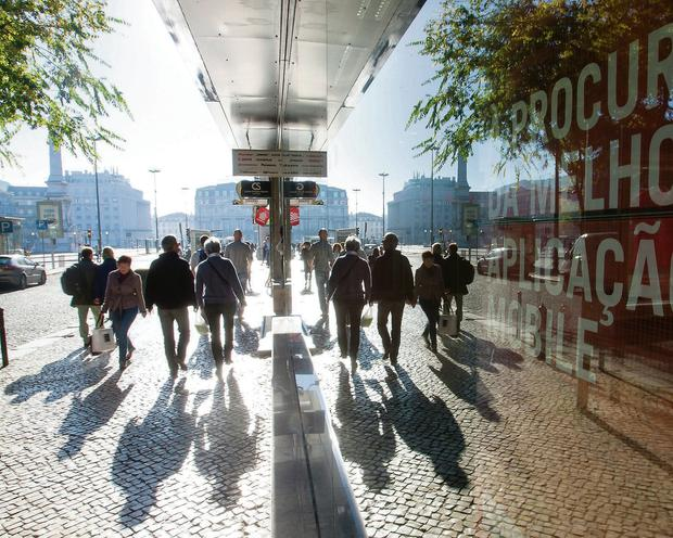 Pedestrians are reflected in the window of a Banco BPI bank branch in Lisbon, Portugal.