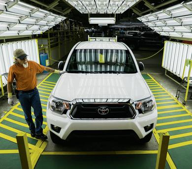 A worker performs a round of quality control checks on a Toyota Tacoma truck at a manufacturing facility in San Antonio, Texas