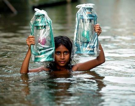 A girl holds up kerosine lamps as she makes her way through a flooded street in Dhaka, Bangladesh. Ireland is said to be vulnerable to climate change.
