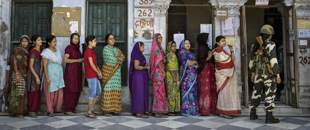 Indians wait in line to vote at a polling station