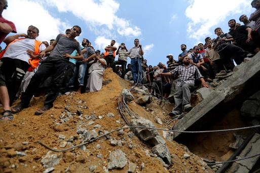 Palestinians on the rubble of a home destroyed by an Israeli strike in Khan Younis in the southern Gaza Strip