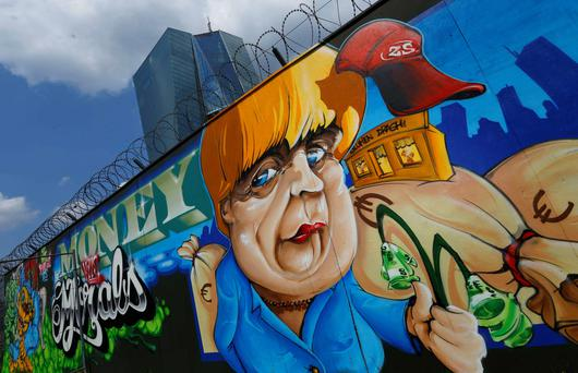 Graffiti of German Chancellor Angela Merkel reading 'Money vs Morals, at the site for the new ECB headquarters in Franfurt.