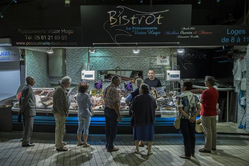 Customers look at fresh seafood on a fish stall at the Victor Hugo indoor market in Toulouse, France