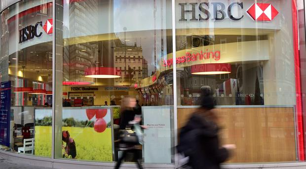 Pedestrians walk past a branch of HSBC in central London November 3, 2014. HSBC's profits fell short of expectations in the third quarter after the bank set aside $1.8 billion for misconduct settlements and compensation for customers, including a potential fine for rigging currency markets. REUTERS/Toby Melville (BRITAIN - Tags: BUSINESS)