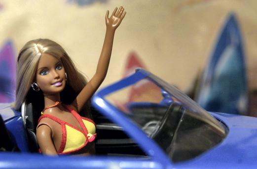 Cali Girl Barbie waves from the front seat of a Chevy SSR during the Toy Fair in New York on February 17, 2004. Photographer: Daniel Acker/Bloomberg News.