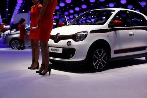 Employees stand beside a display of the latest Renault Twingo car at last autumn's Paris Motor Show