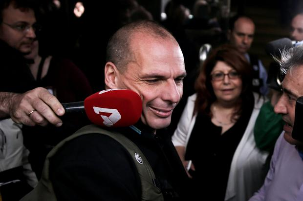 Greek Finance Minister Yanis Varoufakis arrives at his ministry in Athens yesterday, while tax officers demonstrate over pay issues in their sector