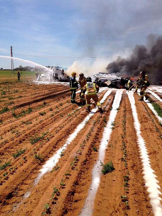 A handout picture taken and released on May 9, 2015 by Bomberos del Ayuntamiento de Sevilla shows firemen working next to wreckage of an Airbus A400M military transport plane after crashing near Sevilla. An Airbus A400M military transport plane carrying