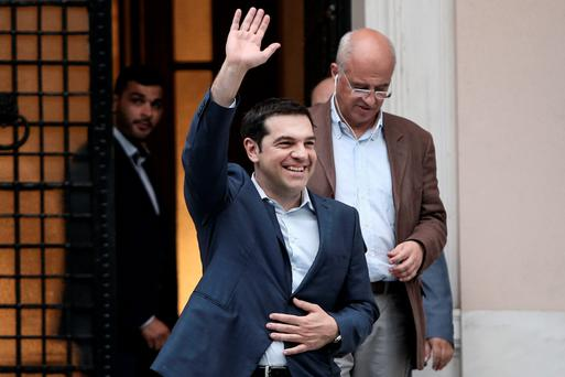 Greek Prime Minister Alexis Tsipras waves as he leaves his office at Maximos Hall after a marathon meeting in Athens