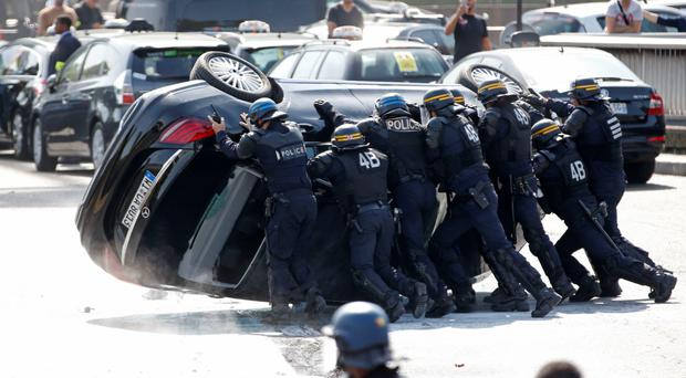 Riot police push an overturned car as striking taxi drivers demonstrate at Porte Maillot to block traffic on the Paris ring road