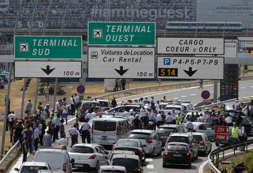 French striking taxi drivers block the access to Orly airport, south of Paris, France, during a national protest against car-sharing service Uber June 25, 2015. French taxi drivers stepped up protests against U.S. online cab service UberPOP on Thursday, blocking road access to airports and train stations in Paris and other cities. REUTERS/Christian Hartmann