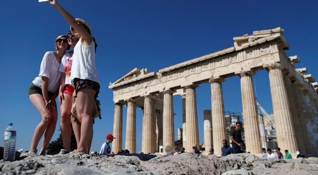 A group of tourists take a selfie in front of the temple of the Parthenon atop the Acropolis in Athens, Greece