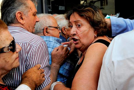 A pensioner wearing an oxygen line tries to enter a crowded National Bank branch to get her pension in Thessaloniki