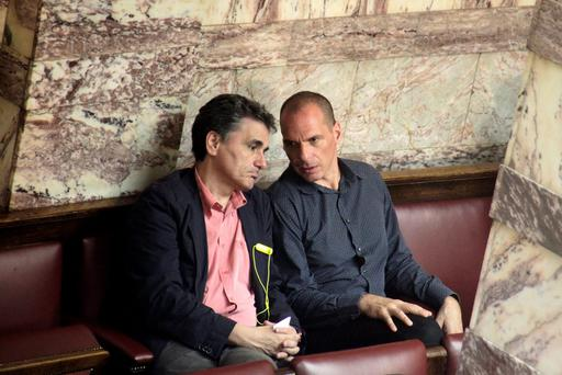 Greek Finance Minister Euclid Tsakalotos (L) and former finance minister Yanis Varoufakis talk during a parliamentary session in Athens