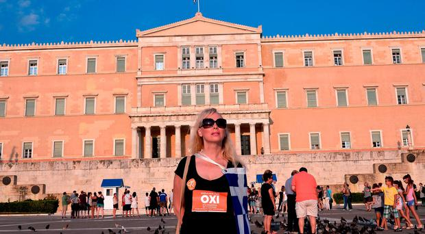 An anti-austerity protester stands in front of Greek parliament in Athens - fears of a Greek exit from the Euro zone has eased