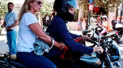 Outgoing Greek Finance minister Yanis Varoufakis leaves on his motorcycle with his wife Danai after his resignation at the ministry of Finance in downtown Athens this week