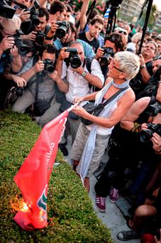 A protester attracts a swarm of photographers as she burns a Syriza flag outside the Greek parliament in Athens