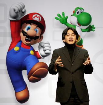 Nintendo CEO Satoru Iwata with some of the company's iconic characters including Mario and Yoshi