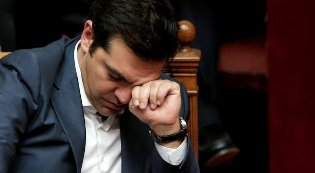 Prime Minister Alexis Tsipras rubs his eyes as the Greek parliament debates the new legislation into the early hours of the morning