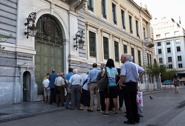 People line up outside a National Bank branch in Athens