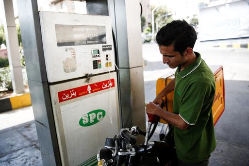 A motorcyclist fills his tank with petrol at a gas station showing the logo of Shiraz Petroleum Co. (SPC) in Tehran, Iran, on Saturday, Aug. 22, 2015. Iran plans to raise oil production