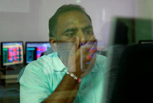A broker reacts while trading at his terminal in Mumbai yesterday. India's BSE index fell more than 5pc as world markets slumped