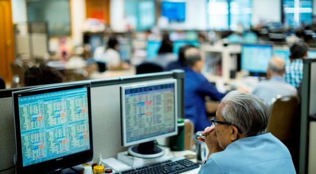 A broker sits in front of screens showing share prices at a securities brokerage in Hong Kong