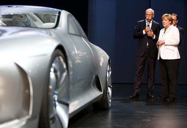 German Chancellor Angela Merkel listens to Daimler CEO Dieter Zetsche next to a Mercedes-Benz Concept IAA car