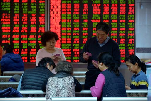 Investors play cards in front of screens showing stock market movements at a securities company in Beijing on Friday Photo: AFP/Getty Images
