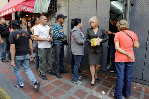Locals queue to buy goods at a supermarket in Caracas. Photo: Reuters