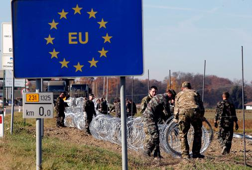 Border guards erecting a fence in Slovenia late last year. European leaders meet next week to discuss the migrant crisis Photo: Reuters