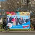 Cyclists pass an Alternative for Germany (AfD) campaign poster in Magdeburg, Saxony-Anhalt state, Germany