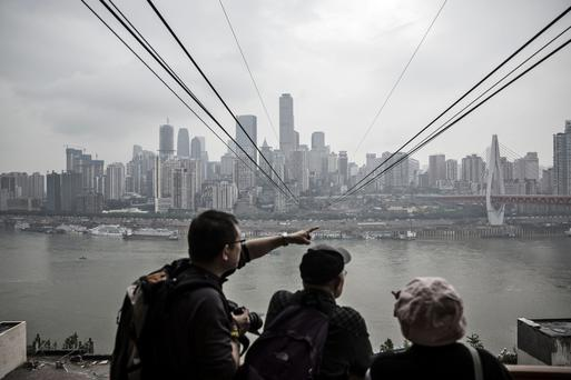 Passengers looks out at the city skyline as they wait to board a cable car at a Yangtze River Cableway station in Chongqing, China,
