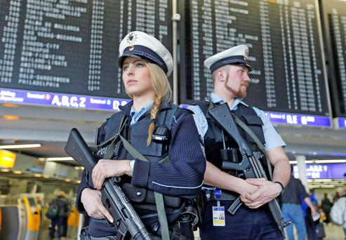 German police officers guard a terminal at Frankfurt Airport during tighter security measures following deadly attacks by extremists in Brussels in March