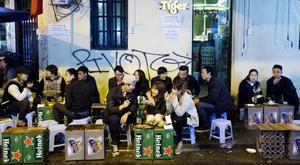 Customers sit eating and drinking over crates featuring branding for Heineken and Tiger beers at an outdoor restaurant in the Old Quarter of the northern city of Hanoi