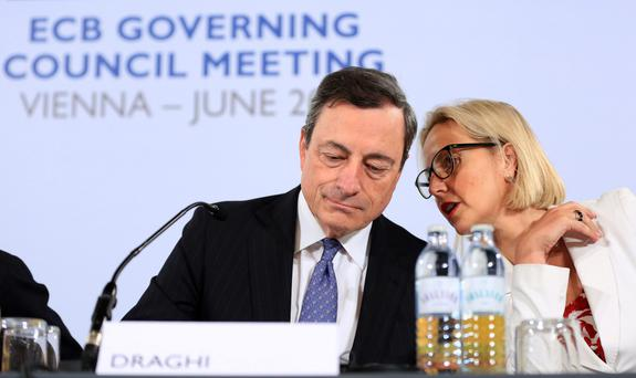 Mario Draghi, president of the European Central Bank, listens to Christine Graeff, the bank's director general for communications