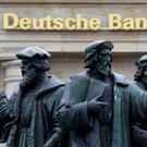 A statue is pictured next to the logo of Germany's Deutsche Bank in Frankfurt. Photo: Reuters
