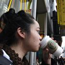 A woman drinks Starbucks coffee outside a New York McDonald's restaurant