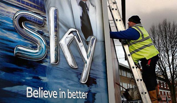 A Sky poster is erected by a worker in Birmingham