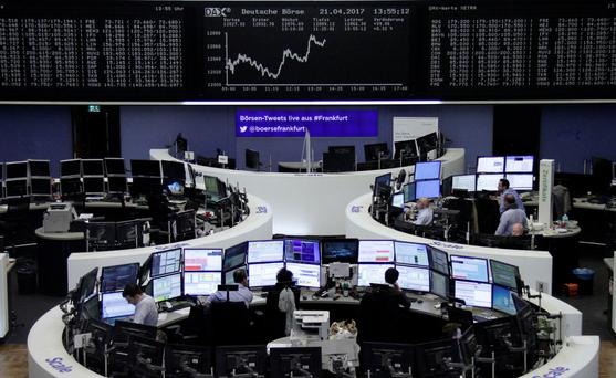 Traders work at their desks in front of the German share price index DAX board at the stock exchange in Frankfurt