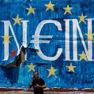 A pedestrian in Athens uses a mobile phone as he smokes a cigarette in front of graffiti street art on a billboard showing the stars of the European Union