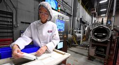 Lea Mohr prepares packaged meals for a MATS-B machine with new microwave technology at an Ameriqual facility in Indiana. Photo: Reuters